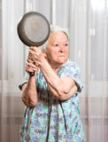 Angry old woman with a pan Stock Photography