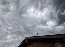 Angry clouds over a house. Angry and ominous clouds overtop of a house with a weather vain in silhouette stock photo