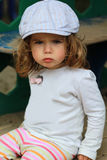 Angry one year old girl in a checked cap sitting offended on playground royalty free stock photography
