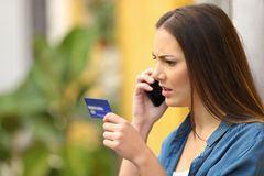 Angry online shopper complaining talking on phone. Holding credit card in the street royalty free stock images