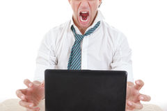 Angry and overworked half face business man with laptop in front. Photo of exhausted, angry and overworked half face business man with laptop in front of him on Royalty Free Stock Photos