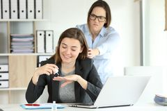 Angry partner trying to kill to her lazy colleague. At office royalty free stock images