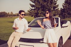 Angry partners on journey trip, escape drive ride, guy in formal. Wear sist on a hood, lady leaning it. Driver and frustrated chic are arguing, fault, guilt Royalty Free Stock Images