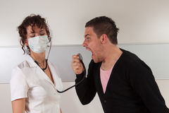 Angry patient. Guy screaming in a stethoscope Stock Image