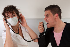 Angry patient. Guy screaming in a stethoscope royalty free stock photo