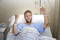 Angry patient man at hospital room lying in bed pressing nurse call button feeling nervous and upset Stock Photography