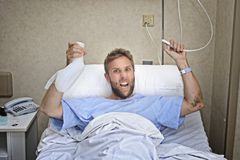 Angry patient man at hospital room lying in bed pressing nurse call button holding potty Stock Photos