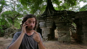 Angry phone call, ruins in tropical jungle Stock Image