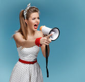 Angry pin-up girl shouting into a megaphone, mouthpiece, speaking trumpet. Filmmaking or film production concept Royalty Free Stock Photos