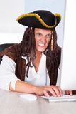 Angry Pirate Using Computer. Portrait Of A Angry Pirate Clenching His Teeth Using Computer Royalty Free Stock Images