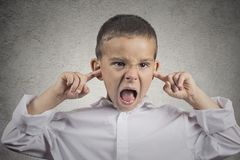 Angry pissed off boy plugs his ears with fingers Stock Photography
