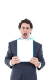 Angry pissed off man holding up a banner or notes against a whi. Angry pissed off man in suit holding up a banner or notes against a white background and showing Royalty Free Stock Photography