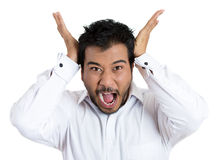 Angry pissed off young man with hands on head and mouth wide open Stock Photography