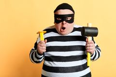 Angry plump criminal in striped clothes preparing for crime. Isolated yellow background. studio shot royalty free stock photos
