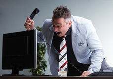 Angry plump manager destroying his pc. Angry boss about to destroy his pc monitor found guilty to be in the wrong place in the wrong moment Stock Image