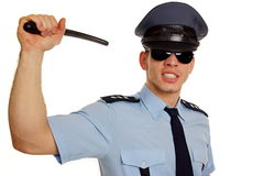 Angry policeman with police baton. Stock Images