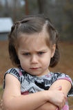 Angry and Pouting. Arms crossed and eyebrows puckered, this little girl is upset and pouting.  She is standing outside and image is closeup Stock Images