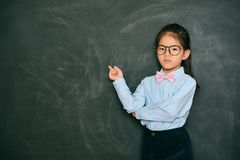 Angry pretty little teacher pointing blackboard royalty free stock images