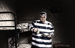 Angry prisoner wearing prison uniform holding aluminum dishes in Stock Photo