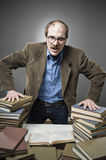 Angry Professor with a stack of books. Angry professor with a mad expression royalty free stock photos