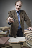 Angry Professor with a stack of books. Angry professor with a mad expression stock photo