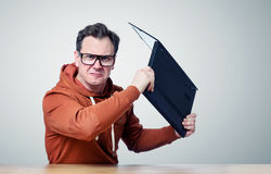 Angry programmer with glasses throwing laptop into the camera. On background Stock Photography