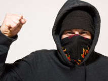 Angry Protester or Mugger. A hooded, masked angry man with a raised fist and intent eyes stock photo