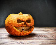 Angry pumpkin lantern jack on a wooden table. On a black background Royalty Free Stock Images