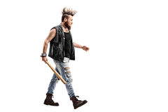 Angry punk rocker holding a baseball bat. Full length profile shot of an angry punk rocker walking with a baseball bat in his hand isolated on white background Royalty Free Stock Photos
