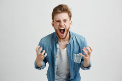 Angry rage young man with beard shouting screaming gesturing over white background. Copy space Royalty Free Stock Photos