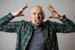 Angry rage young man shouting over beige background. Royalty Free Stock Photography