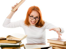 Angry red-haired girl in glasses with books Stock Image