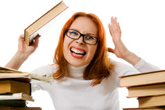 Angry red-haired girl in glasses with books. Royalty Free Stock Photos