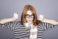 Angry red-haired girl in glasses and scarf. Royalty Free Stock Image