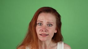 Angry red haired woman on green chromakey. Studio portrait of a young red haired woman looking angry. Ginger female arguing with you, posing on green chromakey stock video footage