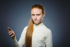 Angry redhead girl with cell phone. isolated on gray Royalty Free Stock Photo