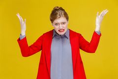 Angry redhead woman in red suit roar. Studio shot, isolated on yellow background royalty free stock image