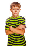 Angry restless evil dark blond kid in a striped Stock Photos