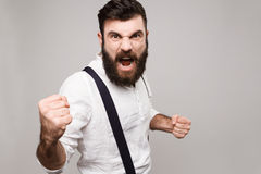 Angry rude young handsome man shouting over white background. Stock Image