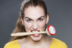 Angry 20s girl with dish brush in teeth for cleaning and washing revolt at home Stock Image