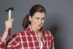 Angry 30s woman holding hammer for aggression or self-defense Royalty Free Stock Images