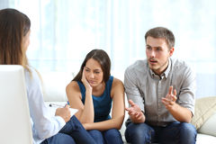 Angry and sad couple talking with a marriage counselor. Angry husband and sad wife talking with a marriage counselor before breaking up sitting on a sofa at home Royalty Free Stock Photography