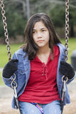 Angry, sad preteen girl on swing Stock Image