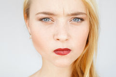 Angry sad red-haired woman portrait. Young female with very serious and blaming look, pursed lips. Angry, frowning, grumpy carroty girl close-up Stock Photos