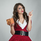 Angry Santa girl holding golden gift box and scolding finger looking at camera Stock Images