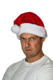 Angry santa. Portrait of a young caucasian male upset and wearing a santa hat Royalty Free Stock Photography