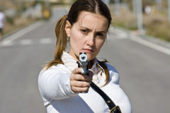 Angry scholar. Scholar girl pointing at camera with gun Stock Photo