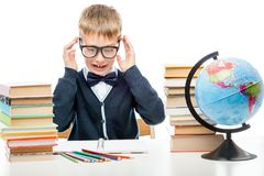 Angry schoolboy with books at the table on a white Royalty Free Stock Photos