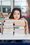 Angry Schoolgirl Resting Chin On Books. Portrait of angry little schoolgirl resting chin on stack of books at desk in classroom Stock Image