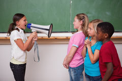 Angry schoolgirl screaming through a megaphone. To her classmates in a classroom Stock Images